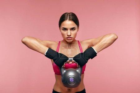 Photo pour Exercice sportif. Entraînement de femme athlétique avec haltère, poids de levage féminin sur fond rose. Haute résolution - image libre de droit