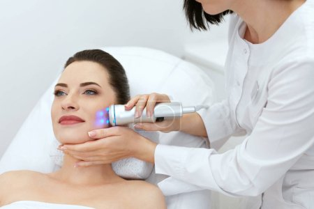 Photo pour Beauté. Femme faisant des bleu traitement Facial léger sur la peau du visage à la clinique de la cosmétologie. Haute résolution - image libre de droit