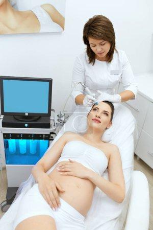 Photo pour Soins de la peau. Femme enceinte sur le visage nettoyage à la clinique de beauté. Cosmetologist Using Hydra Vacuum Cleaner For Cosmetology Peeling. Haute résolution - image libre de droit