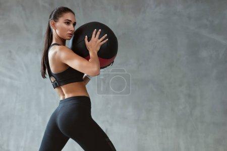 Photo pour Entraînement de femme de sport dans la mode vêtements de sport noirs, entraînement avec balle de remise en forme sur fond gris. Haute résolution - image libre de droit