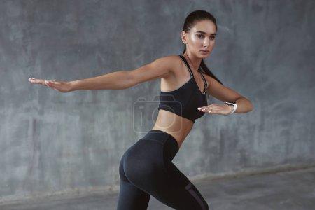 Photo pour Body Fitness. Formation de la femme à la mode Black Sportwear, étirement des mains sur fond gris. Haute résolution - image libre de droit