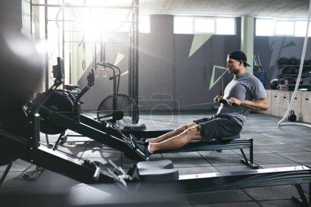 Photo pour Cardio Training. Sport homme exerce sur rameur au gymnase, athlète, faire des exercices fonctionnels. Haute résolution - image libre de droit