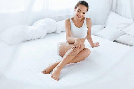 Photo pour Soins de la peau corporelle. Belle femme touchant longues jambes assises sur lit blanc dans la lumière intérieure. Épilation. Haute résolution - image libre de droit