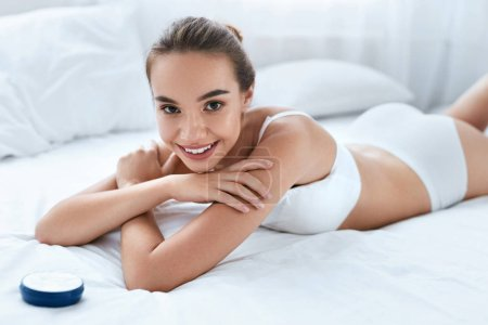 Photo for Beauty Skin Care. Happy Woman With Beautiful Soft Skin And Body Cream Lying On White Bed. High Resolution - Royalty Free Image