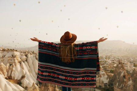 Photo pour Voyage. Femme en chapeau s'amuser à l'extérieur, profiter du paysage avec des ballons à air chaud dans le ciel. Haute résolution - image libre de droit