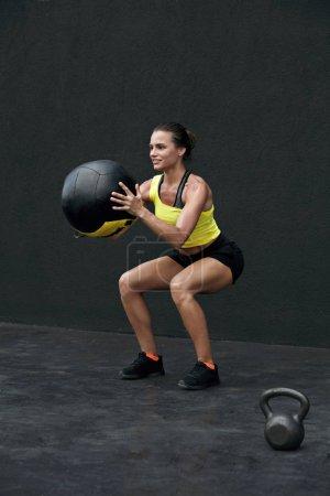 Photo pour Entraînement. Femme de remise en forme faisant de l'exercice de squat avec balle médicale au gymnase. Sport modèle féminin en vêtements de sport et fit body squatting, l'exercice à l'extérieur sur la rue - image libre de droit