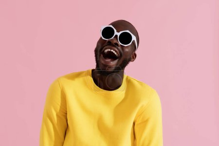 Fashion. Smiling black man in sunglasses colorful portrait
