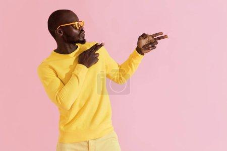 """Photo pour La mode. Homme noir avec des lunettes de soleil élégantes et des vêtements amusants. Portrait coloré de mannequin masculin en lunettes jaunes et sweat-shirt tenant les mains """"finger gun"""" sur fond rose - image libre de droit"""