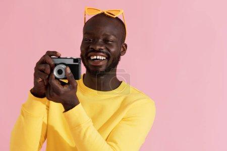 Foto de Feliz hombre fotógrafo con cámara de fotos en el fondo rosa colorido. Retrato de la sonriente modelo negra masculina en ropa de moda amarilla tomando fotos en el estudio - Imagen libre de derechos
