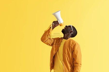 Photo pour Publicités. Annonce criante d'homme dans le mégaphone sur le fond jaune. Verticale du modèle masculin américain africain dans l'usure de mode utilisant le haut-parleur en studio - image libre de droit