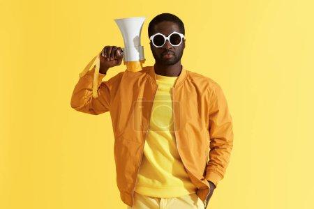 Photo pour Homme noir dans des lunettes de soleil de mode avec le portrait de mégaphone sur le fond jaune. Modèle mâle dans les vêtements et les lunettes élégants avec le haut-parleur en studio - image libre de droit