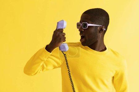 Foto de Hombre sorprendido en gafas de sol con teléfono morado sobre fondo amarillo. Retrato de modelo hombre negro conmocionado con expresión emocional de la cara asustada con teléfono en el estudio - Imagen libre de derechos