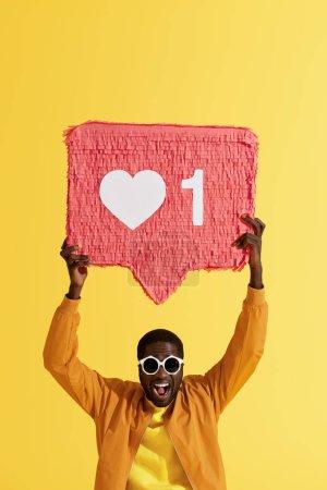 """Photo pour Comme ça. Homme noir souriant avec comme icône, coeur pinata sur fond jaune. Portrait studio d'un homme joyeux avec un énorme bouton de signe """"j'aime"""", symbole des médias sociaux - image libre de droit"""