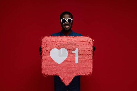 Photo pour Heureux homme noir avec les médias sociaux comme icône pinata sur fond rouge. Portrait de modèle masculin souriant dans des lunettes de soleil démontrant énorme signe de notification cardiaque - image libre de droit