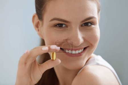 Photo for Vitamin. Smiling woman with omega 3 pill, fish oil capsule in hand. Closeup portrait of beautiful girl taking vitamin D, E supplement. Diet nutrition concept - Royalty Free Image