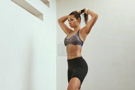 Photo pour Femme en vêtements de sport après l'entraînement de remise en forme à l'extérieur. Femme athlétique avec corps en forme en vêtements de sport et fitness tracker sur la main attacher les cheveux - image libre de droit