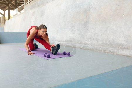 Photo pour Femme. Entraînement de forme physique pour la flexibilité sur le tapis de yoga au stade extérieur. Sexy Girl In Fashion Tenue de sport Formation à l'extérieur. Fit femelle avec le corps musculaire fort faisant l'exercice d'étirement. - image libre de droit
