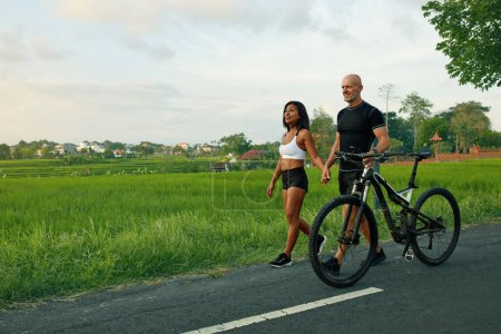 Photo for Sportive Couple Walking Bike On Road. Asian Woman And Caucasian Man Walking By Hands With Bicycles And Talking Against Green Tropical Landscape. - Royalty Free Image