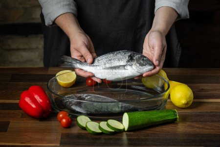 Chef cooking sea fish with citrus and vegetable ingredients on wooden table