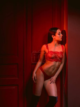 Photo for Sensual brunette woman in lace lingerie posing in red light - Royalty Free Image