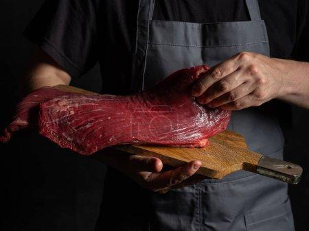 Photo pour Chef tenant de la viande crue - image libre de droit