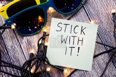 Stick with it motivational concept in business on notepaper. Two sunglasses of different colors with retro wooden background. LED lights are shown in various order. Business concept.