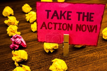 Conceptual hand writing showing Take The Action Now Motivational Call. Business photo showcasing Act Start Promptly Immediate Instantly Paperclip retrain pink card with letters wooden floor hunch
