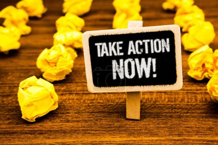 Handwriting text writing Take Action Now Motivational Call. Concept meaning Urgent Move Start Promptly Immediate Begin White text black paint wooden board clip desk yellow paper notes warning