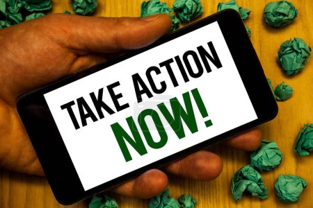 Handwriting text Take Action Now Motivational Call. Concept meaning Urgent Move Start Promptly Immediate Begin Hand holding phone white screen written words crumbled green notes paper
