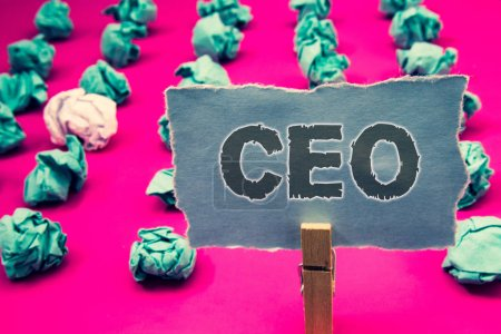 Handwriting text writing Ceo. Concept meaning Chief Executive Officer Head Boss Chairperson Chairman Controller Clothespin holding green paper crumpled papers ideas mistakes several tries