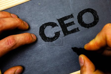 Word writing text Ceo. Business concept for Chief Executive Officer Head Boss Chairperson Chairman Controller Man hold holding black marker markers notebook wood wooden background