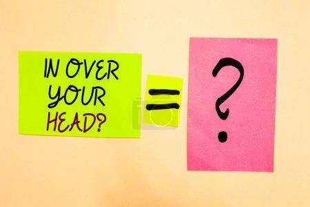 Foto de Escribiendo una nota que muestra la pregunta de In Over Your Head. Exposición de fotos de negocios Para estar involucrado en un problema de situación difícil Escrito en verde nota adhesiva en amarillo y signo de interrogación en papel rosa - Imagen libre de derechos