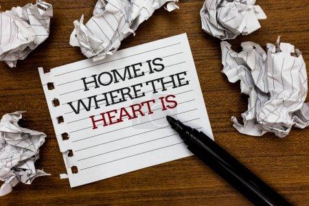 Photo pour Texte signe montrant Accueil est lorsque le cœur est conceptuel photo que votre maison où vous sentirez à l'aise et heureux papier grumeaux n'est posé au hasard autour bloc-notes blanc tactile stylo noir sur plancher bois - image libre de droit