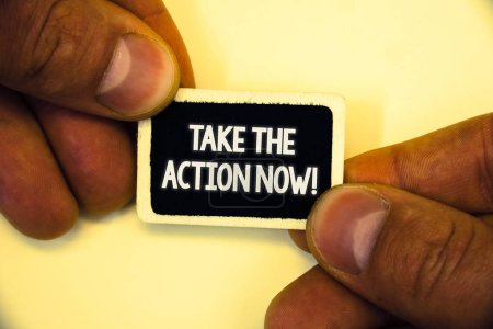 Word writing text Take The Action Now Motivational Call. Business concept for Act Start Promptly Immediate Instantly Two hands hold small black card focused white massage hoary background.