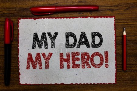 Photo for Text sign showing My Dad My Hero. Conceptual photo Admiration for your father love feelings emotions compliment Red bordered white page centered some texts wooden desk pen pencil - Royalty Free Image