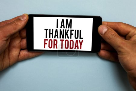 Photo for Word writing text I Am Thankful For Today. Business concept for Grateful about living one more day Philosophy Human hand hold smartphone with red and black letters on shadow blue floor - Royalty Free Image
