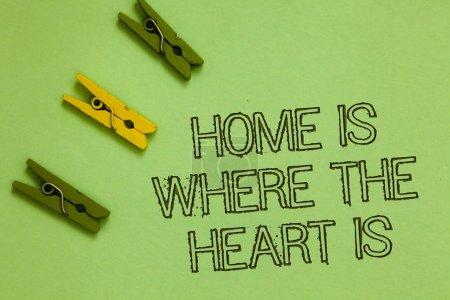 Photo pour Mot écrit texte Accueil est lorsque le cœur est concept commercial pour votre maison est où vous sentirez à l'aise et heureux mots contour vert moyen jaune trombone sur terrain de couleur olive - image libre de droit