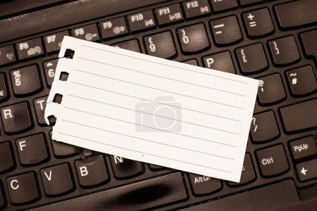 Negocio de diseño Plantilla vacía aislada Plantilla de diseño gráfico minimalista para publicidad Índice de página en espiral desgarrado en blanco Tamaño de papel forrado acostado en el teclado del ordenador portátil