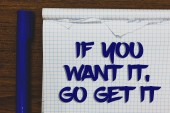 Writing note showing If You Want It, Go Get It.. Business photo showcasing Make actions to accomplish your goals wishes Written white notepad on grey wooden background beside blue marker.