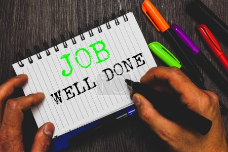 Handwriting text writing Job Well Done. Concept meaning Well Performed You did it Cheers Approval Par Accomplished Man holding marker notebook paper communicating ideas Wooden background.
