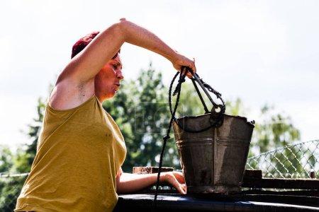Photo pour Vue latérale d'une femme tenant un seau en métal avec une ficelle. La dame qui travaille dur récupère l'eau du puits naturel. Typique ménage quotidien corvée. Scénario de vie à la campagne - image libre de droit