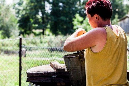 Photo pour Vue arrière d'une femme tenant un seau métallique. La mère qui travaille dur se prépare à aller chercher de l'eau dans le puits de la cour. Typique ménage quotidien corvée. Scénario de vie à la campagne - image libre de droit