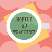 Writing note showing Mobile Ad Tracking. Business photo showcasing monitor brand perforanalysisce including advertising awareness Top View of Drinking Cup Filled with Beverage on Color Paper photo.