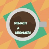 Text sign showing Remain A Dreamer. Conceptual photo they spend lot of time thinking about and planning things Top View of Drinking Cup Filled with Beverage on Color Paper photo.