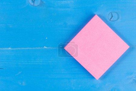 Gros plan vue colorée en bois trous écrasés fond notes collantes tampons milieu. Feuille de papier carré bois. Ecrire des idées, des projets, des objectifs, des messages. Bureau, école à domicile