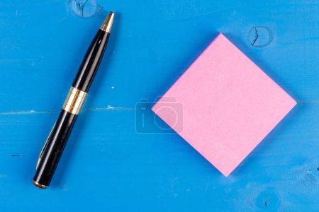 Gros plan vue en bois coloré trous écrasés fond notes collantes stylo. Feuille de papier carré bille de bois derrière. Ecrire des idées, des projets, des objectifs, des messages .