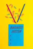 Word writing text Business System. Business concept for A method of analyzing the information of organizations Blank paper sheet message reminder pencils clips colored background.