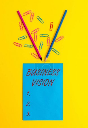 Word writing text Business Vision. Business concept for grow your business in the future based on your goals Blank paper sheet message reminder pencils clips colored background.