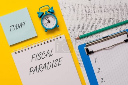 Photo pour Conceptual hand writing showing Fiscal Paradise. Concept meaning The waste of public money is a great concern topic Spiral notepad sheet marker alarm clock wooden background - image libre de droit