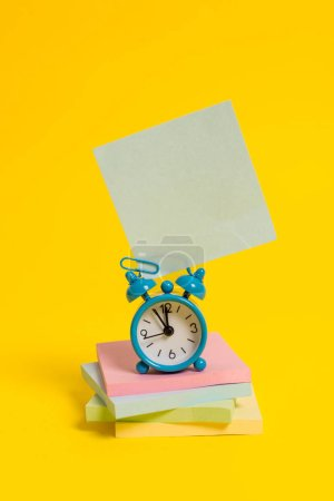 Photo for Metal alarm clock blank sticky note stacked notepads colored background - Royalty Free Image
